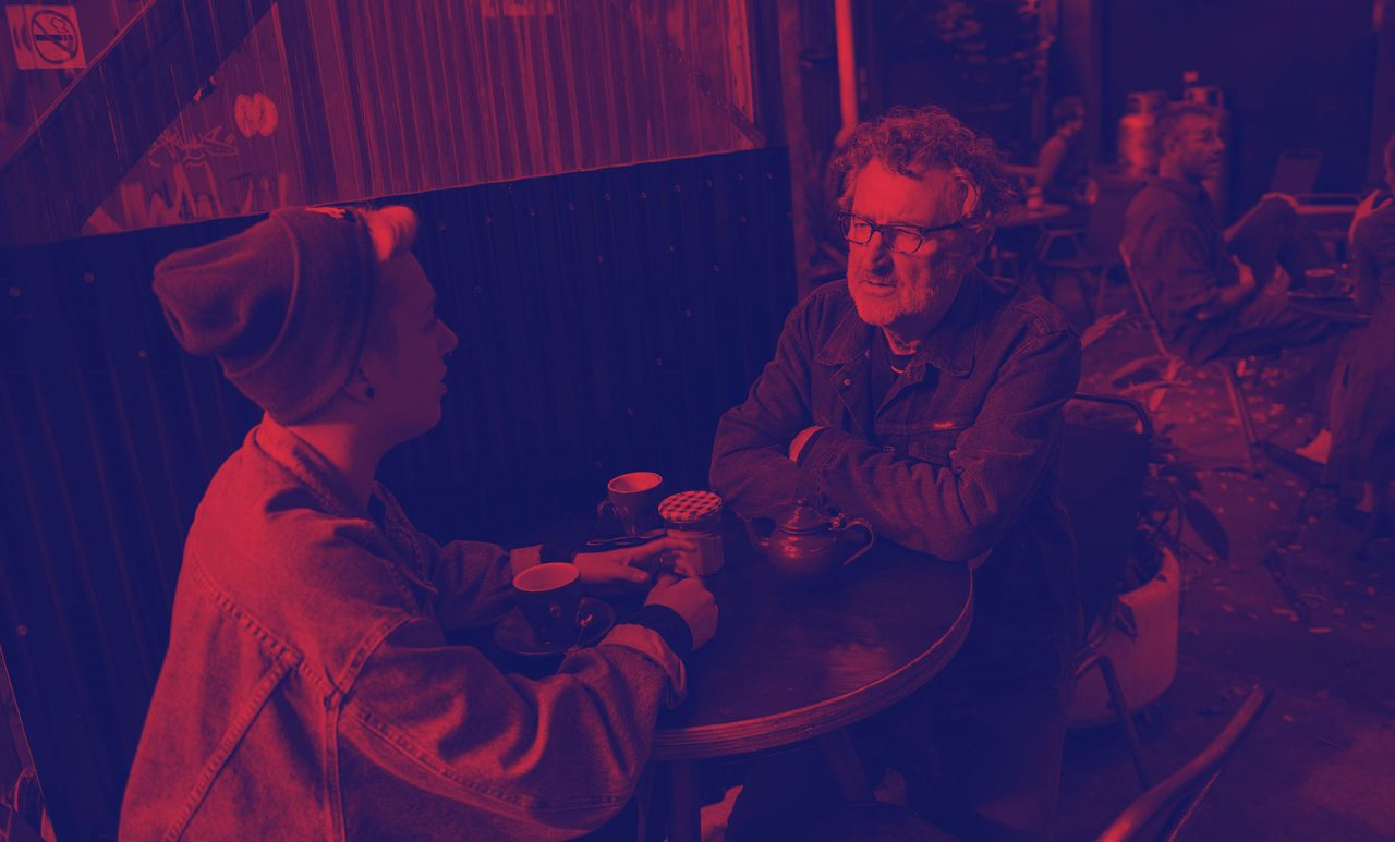 Ben Steer With A Girl At A Table Drinking Coffee With A Red Hue Over The Photo