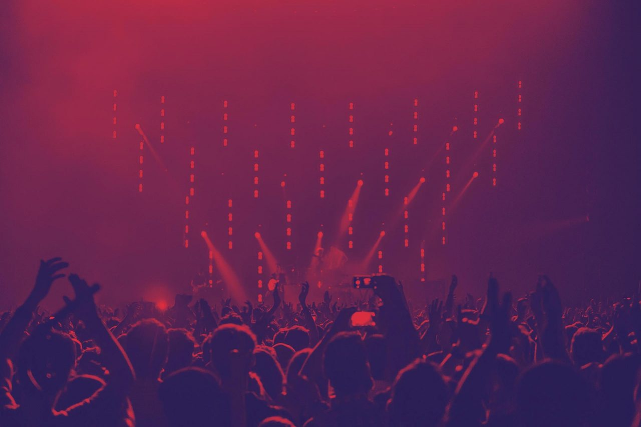 People At A Concert With A Red Hue Over The Photo